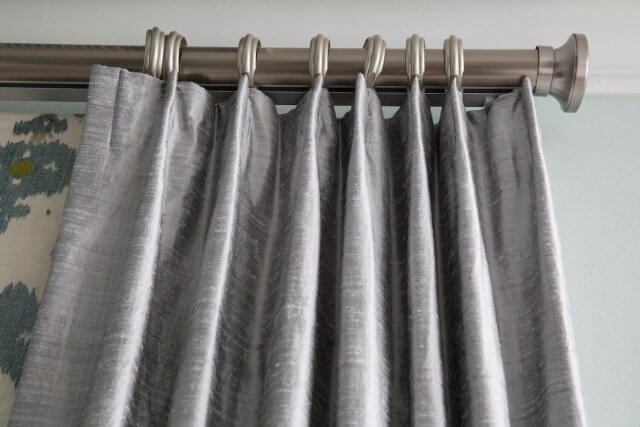 Silvery silk drapes close up